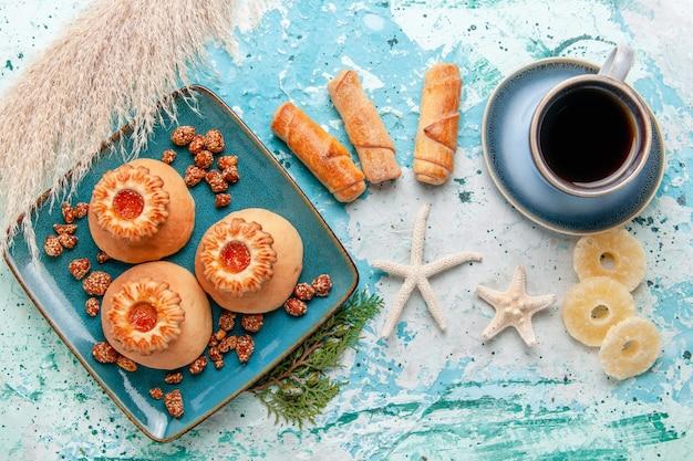 Widok z góry pyszne ciasteczka z suszonymi krążkami ananasa i kawą na jasnoniebieskim biurku herbatniki biszkoptowe w kolorze słodkiego cukru