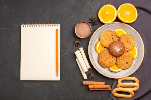 Widok z góry pyszne ciasteczka ze świeżymi pokrojonymi pomarańczami na ciemnym tle ciastko z cukrem ciastko owocowe słodkie