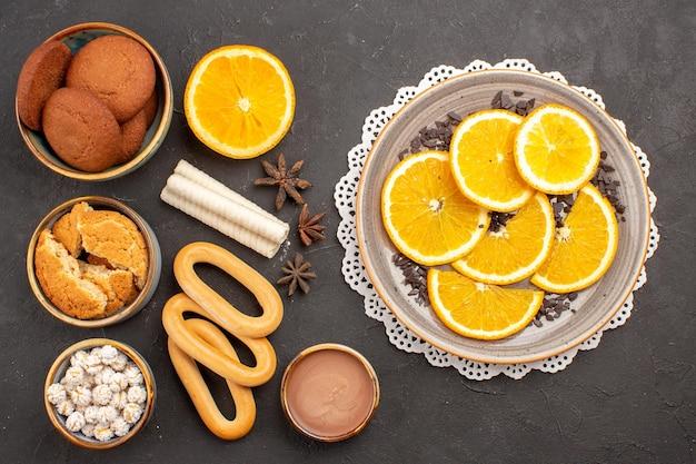 Widok z góry pyszne ciasteczka ze świeżymi pomarańczami na ciemnej powierzchni ciastko biszkoptowe ciasto cukrowe deser słodki