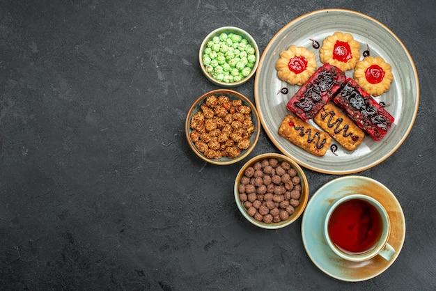 Widok z góry pyszne ciastka owocowe z ciasteczkami i filiżanką herbaty na ciemnym tle ciastko z cukrem ciastko ciastko słodka herbata tea