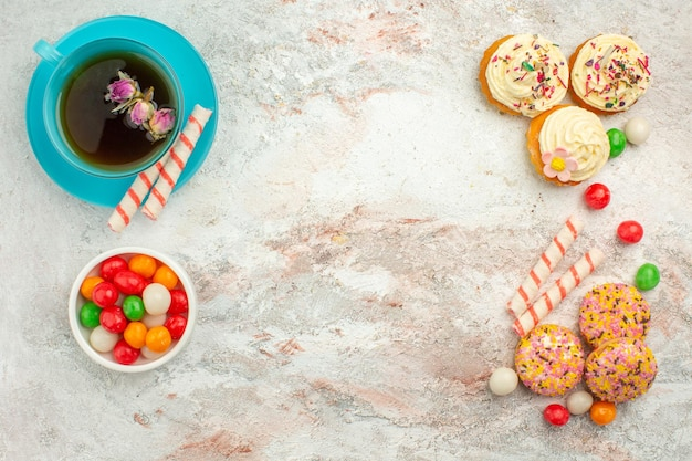 Widok z góry pyszne ciastka z cukierkami i filiżanką herbaty na białej powierzchni ciasto biszkoptowe w kolorze ciasta