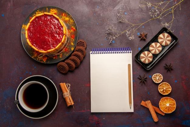 Widok z góry pyszne ciasto deserowe z filiżanką kawy i ciasteczka czekoladowe na ciemnym biurku herbatniki ciastka cukrowe ciasto deser słodki