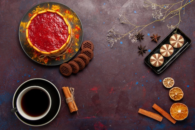 Widok z góry pyszne ciasto deserowe z filiżanką kawy i ciasteczka na ciemnym tle herbatniki ciasteczka cukrowe ciasto deser słodki