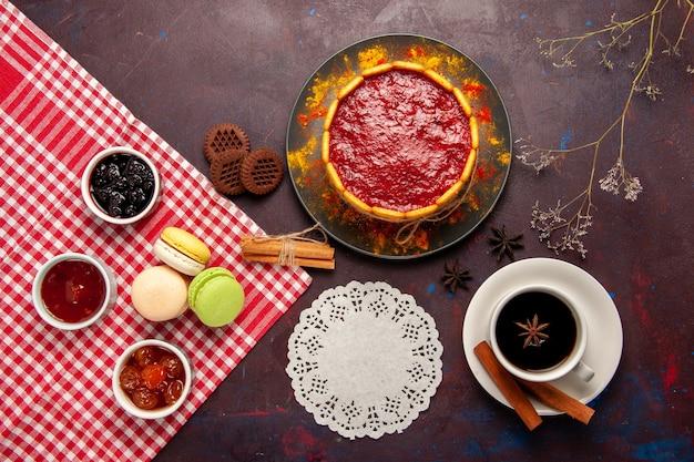 Widok z góry pyszne ciasto deserowe z filiżanką kawy i dżemami owocowymi na ciemnej powierzchni biszkoptowe ciasteczka cukrowe deserowe słodkie