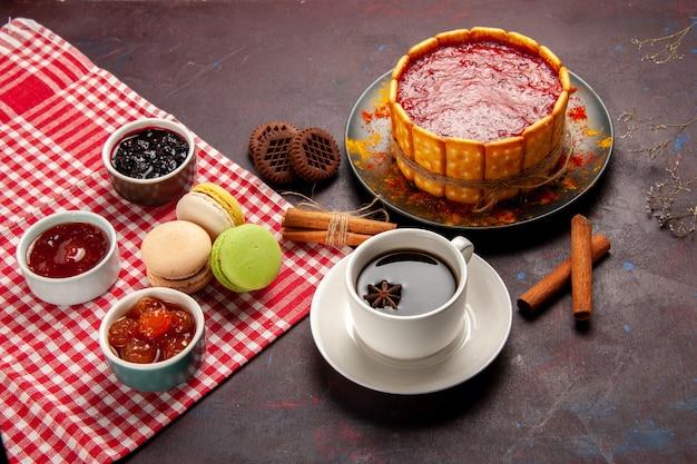 Widok z góry pyszne ciasto deserowe z filiżanką kawy i dżemami owocowymi na ciemnej powierzchni ciastka z cukrem ciastko deserowe słodkie