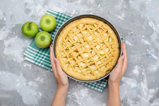 Widok z góry pyszne ciasto jabłkowe okrągłe uformowane wewnątrz patelni z herbatnikiem ciasto świeże zielone jabłka