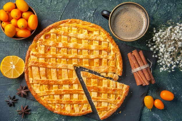 Widok z góry pyszne ciasto kumkwat z pokrojonym kawałkiem i kawą na ciemnym tle