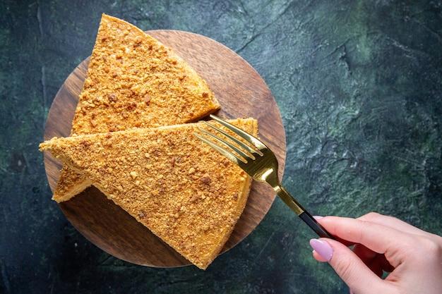 Widok z góry pyszne ciasto miodowe kawałek na okrągłej drewnianej desce ciemnej powierzchni