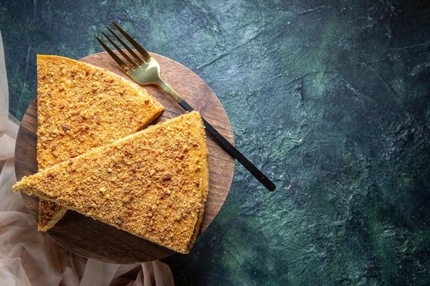 Widok z góry pyszne ciasto miodowe na ciemnej powierzchni okrągłej drewnianej deski
