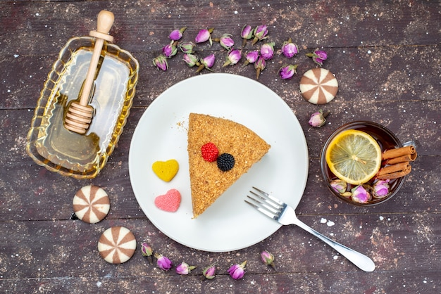 Widok z góry pyszne ciasto miodowe z cukierkami miodem i kwiatami na ciemnym tle cukierek do herbaty ciasto