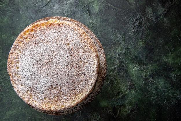 Widok z góry pyszne ciasto miodowe z cukrem pudrem na ciemnej powierzchni okrągłej drewnianej deski
