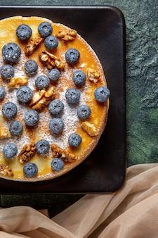 Widok z góry pyszne ciasto miodowe z jagodami i orzechami włoskimi wewnątrz ciemnej powierzchni talerza