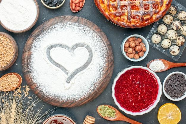 Widok z góry pyszne ciasto owocowe z dżemem z mąki i orzechami na ciemnych owocach słodkie ciasto cukier herbata ciasto deser ciastko biszkoptowe