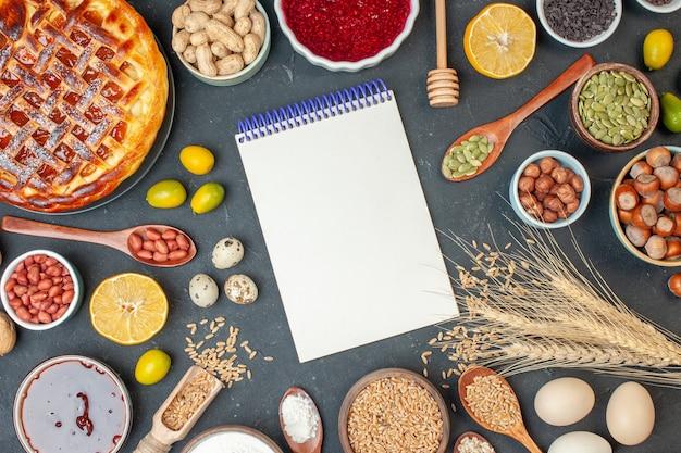 Widok z góry pyszne ciasto owocowe z notatnikiem i orzechami na ciemnym kolorze żywności orzechowej zdjęcie ciasta rodzynki