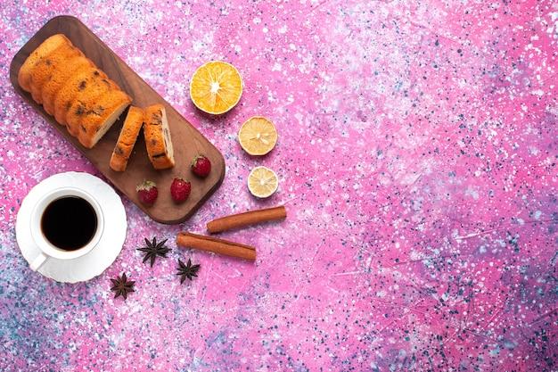 Widok z góry pyszne ciasto słodkie i pyszne w plasterkach z filiżanką herbaty na różowym biurku.