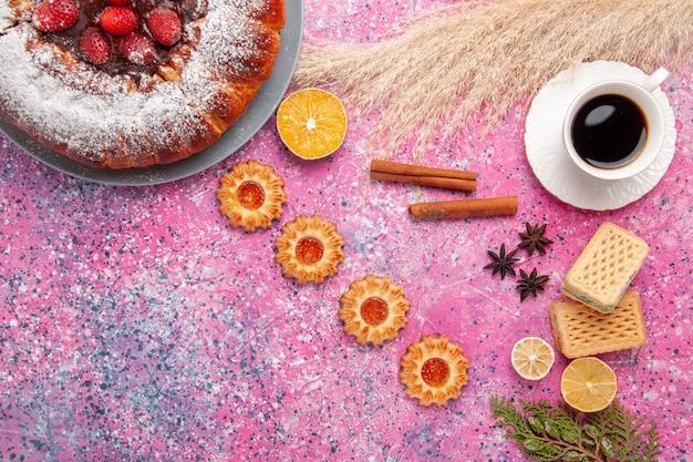 Widok z góry pyszne ciasto truskawkowe ciasto cukrowe w proszku z ciasteczkami waflowymi i filiżanką herbaty na jasnoróżowym cieście na biurku słodkie ciasto cukrowe