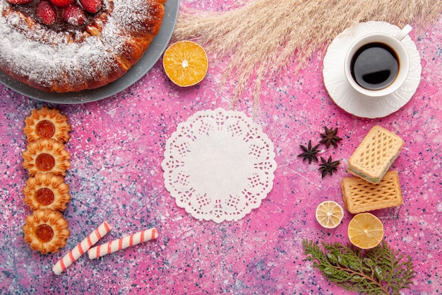 Widok z góry pyszne ciasto truskawkowe ciasto cukrowe w proszku z ciasteczkami waflowymi i filiżanką herbaty na różowym biurku ciasto słodkie ciasto cukrowe