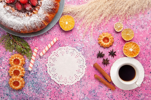 Widok z góry pyszne ciasto truskawkowe cukier puder ciasto z ciasteczkami i filiżanką herbaty na różowym biurku ciasto słodkie ciasteczka cukrowe