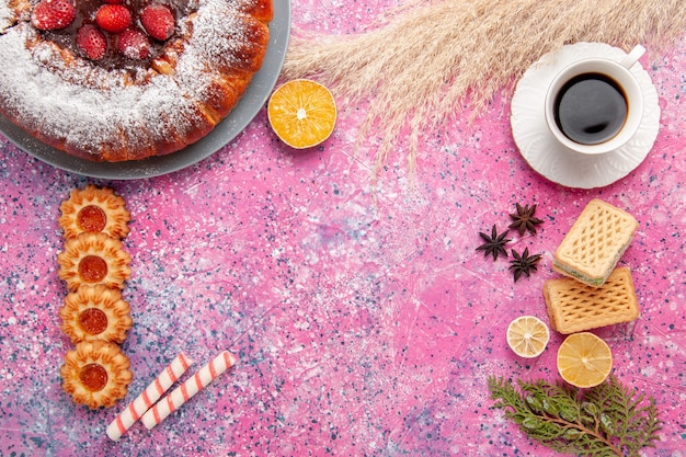 Widok z góry pyszne ciasto truskawkowe cukier puder ciasto z ciasteczkami wafle i filiżanką herbaty na różowym biurku ciasto słodkie ciasteczka cukrowe