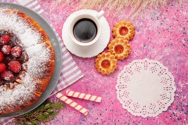 Widok z góry pyszne ciasto truskawkowe cukier puder z ciasteczkami i herbatą na jasnoróżowym tle ciasto słodkie ciasteczka herbatniki herbata