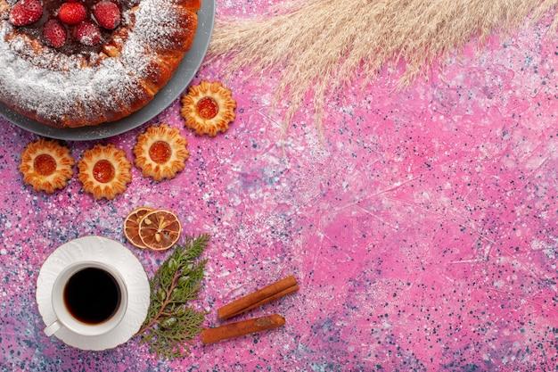 Widok z góry pyszne ciasto truskawkowe cukier w proszku ciasto z ciasteczkami cynamonowymi i filiżanką herbaty na różowym tle ciasto słodkie ciasteczka cukrowe ciasto