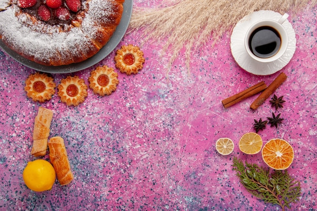 Widok z góry pyszne ciasto truskawkowe cukier w proszku ciasto z ciasteczkami cytrynowymi i filiżanką herbaty na różowym tle ciasto słodkie ciasteczka cukrowe ciasto
