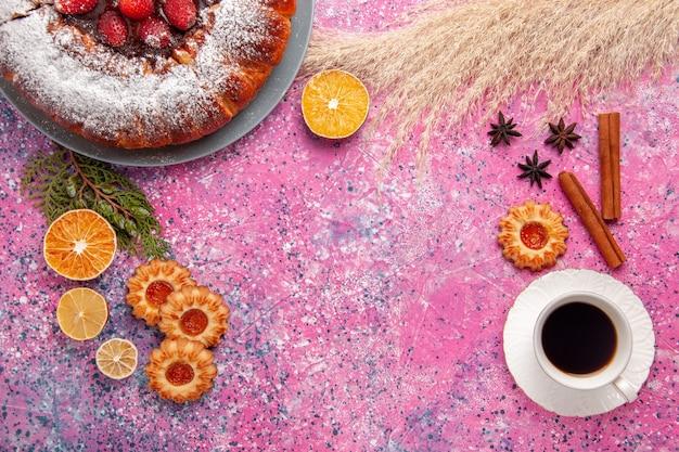 Widok z góry pyszne ciasto truskawkowe cukier w proszku ciasto z ciasteczkami i filiżanką herbaty na różowym tle ciasto słodkie ciastka ciastka cukru ciasto