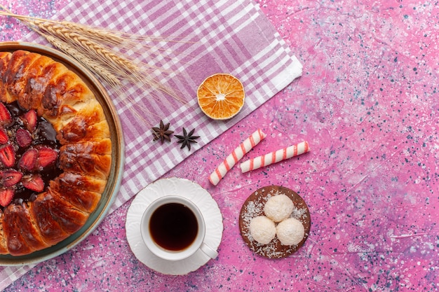Widok z góry pyszne ciasto truskawkowe okrągłe uformowane ciasto owocowe na jasnoróżowym tle