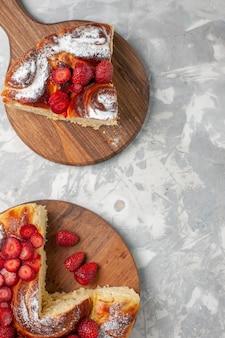 Widok z góry pyszne ciasto truskawkowe pieczone i pyszne deser na białym biurku ciasto biszkoptowe ciasteczka cukrowe słodkie ciasto