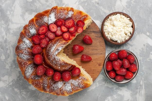 Widok z góry pyszne ciasto truskawkowe pieczone i pyszne deser z twarogiem na białym biurku ciasto biszkoptowo-cukrowe słodkie ciasto