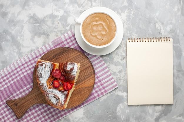 Widok z góry pyszne ciasto truskawkowe pieczone i pyszne kawałek deseru z kawą na białym biurku ciasto biszkoptowe ciasteczka cukrowe słodkie ciasto do pieczenia