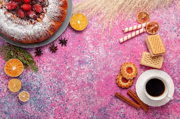 Widok z góry pyszne ciasto truskawkowe z ciasteczkami, herbatą i goframi na jasnoróżowym tle ciasto upiec słodkie ciasto z ciasteczkami ciastka cukru