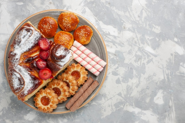 Widok z góry pyszne ciasto truskawkowe z ciasteczkami i ciastkami na białej powierzchni biszkoptowe ciasto cukrowe słodkie ciasteczko