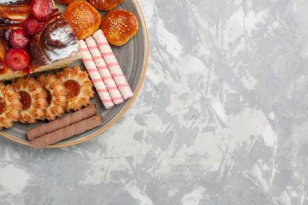 Widok z góry pyszne ciasto truskawkowe z ciasteczkami i ciastkami na jasnobiałym tle biszkoptowe ciasto cukrowe słodkie ciasteczko