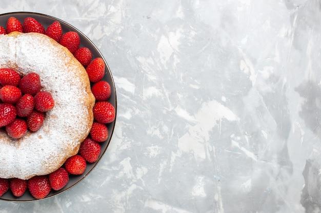 Widok z góry pyszne ciasto truskawkowe z cukrem pudrem na białym tle