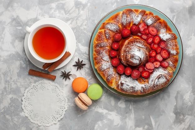 Widok z góry pyszne ciasto truskawkowe z francuskimi makaronikami i filiżanką herbaty na białym biurku ciasto biszkoptowe z cukrem słodkie ciasto do pieczenia