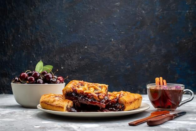 Widok z góry pyszne ciasto truskawkowe z galaretką truskawkową, świeżymi wiśniami i herbatą na lekkim biurku ciasto cukiernicze