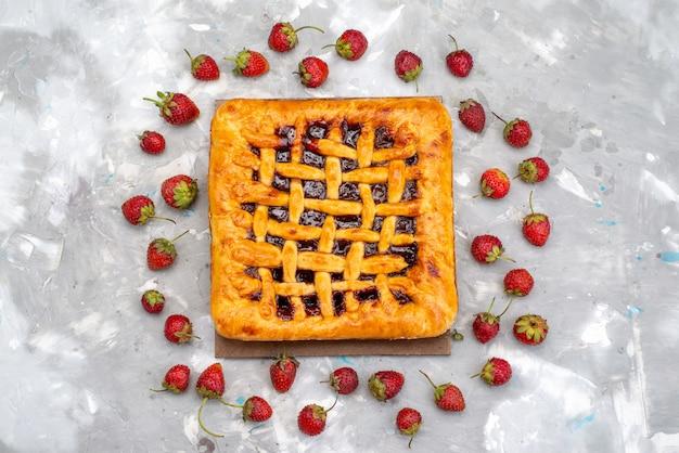 Widok z góry pyszne ciasto truskawkowe z galaretką truskawkową w środku i świeżymi truskawkami na szarym biurku ciasto deserowe