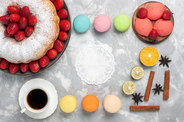 Widok z góry pyszne ciasto truskawkowe z makaronikami i filiżanką herbaty na jasnobiałym tle
