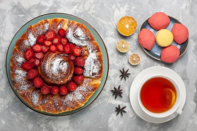 Widok z góry pyszne ciasto truskawkowe z małymi ciastkami i filiżanką herbaty na białej powierzchni ciasto ciasto herbatniki słodka herbata cukrowa piec