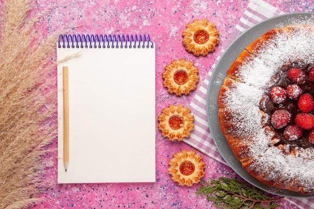 Widok z góry pyszne ciasto truskawkowe z notatnikiem i na jasnoróżowej powierzchni