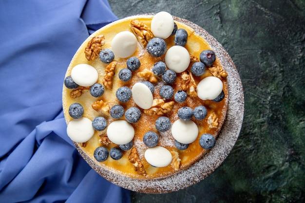Widok z góry pyszne ciasto z ciemną powierzchnią orzechów włoskich, jagód i ciastek