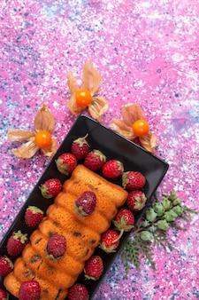 Widok z góry pyszne ciasto z czerwonymi świeżymi truskawkami na różowym biurku.