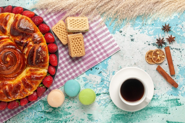 Widok z góry pyszne ciasto z czerwonymi truskawkami francuskimi makaronikami i goframi na niebieskiej powierzchni