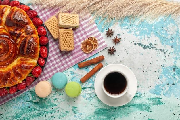 Widok z góry pyszne ciasto z czerwonymi truskawkami i goframi na niebieskim biurku