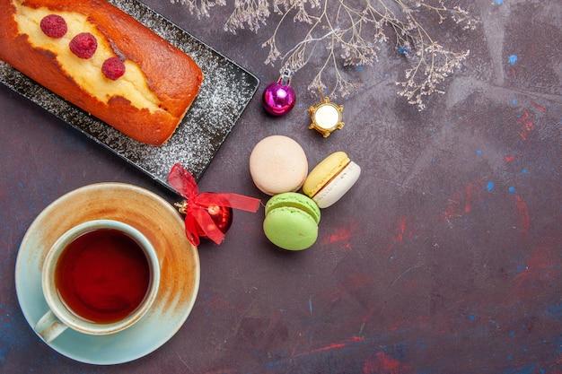 Widok z góry pyszne ciasto z filiżanką herbaty i makaronikami na ciemnej powierzchni