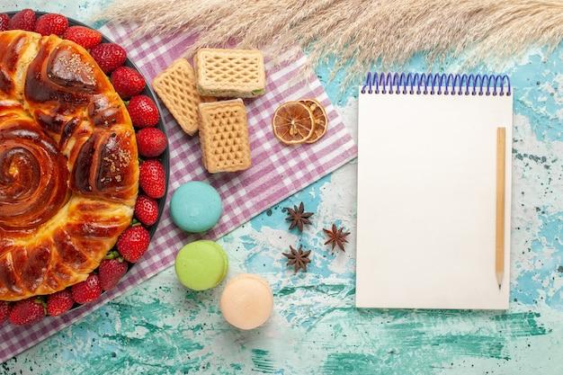 Widok z góry pyszne ciasto z goframi macarons i świeżymi czerwonymi truskawkami na jasnoniebieskiej powierzchni