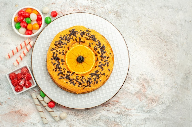 Widok z góry pyszne ciasto z kolorowymi cukierkami na białej powierzchni ciasto herbatniki słodkie ciasto deser tęcza