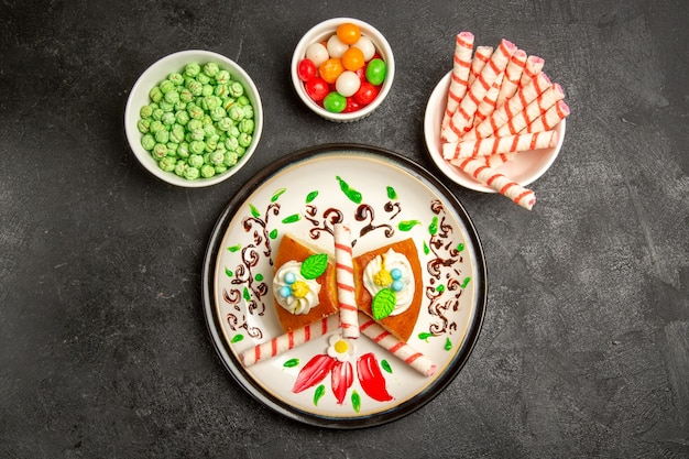 Widok z góry pyszne ciasto z kremem wewnątrz zaprojektowanej płyty z cukierkami na ciemnym tle ciasto słodkie ciasteczko z kremem ciasteczkowym