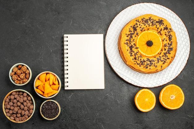 Widok z góry pyszne ciasto z plastrami pomarańczy na ciemnoszarej powierzchni słodkie ciasteczka z herbatnikami owocowymi i herbatą